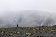 Девушка на наклоне горы на заднем плане утесов в тумане Стоковое фото RF