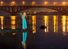Девушка на ноче на речном береге отражение моста Стоковые Изображения