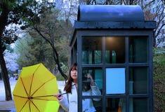 Девушка на общественной кабине таксофона Стоковые Изображения RF