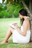 Девушка на парке пишет в ее личном дневнике Стоковое фото RF