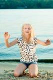 Девушка на песке около воды Стоковые Фото