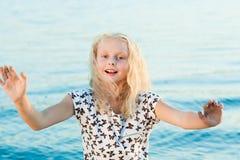 Девушка на песке около воды Стоковые Изображения