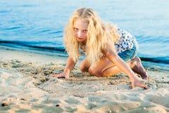 Девушка на песке около воды Стоковое Изображение