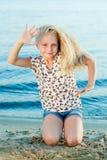 Девушка на песке около воды Стоковая Фотография