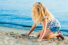 Девушка на песке около воды Стоковое Фото