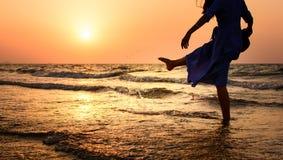 Девушка на пляже на заходе солнца стоковое изображение rf