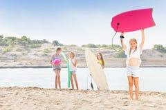 Девушка на пляже с доской тела и ее fiends Стоковая Фотография