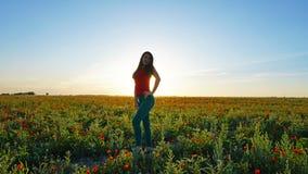 Девушка на полях мака Красные цветки с зелеными стержнями, огромными полями Яркие лучи солнца стоковые изображения rf