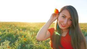 Девушка на полях мака Красные цветки с зелеными стержнями, огромными полями Яркие лучи солнца стоковое фото