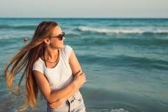 Девушка на предпосылке захода солнца моря Стоковые Изображения