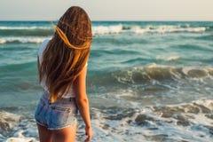 Девушка на предпосылке захода солнца моря Стоковое Фото
