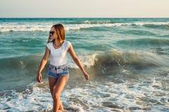Девушка на предпосылке захода солнца моря Стоковое Изображение RF