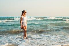 Девушка на предпосылке захода солнца моря Стоковые Фотографии RF
