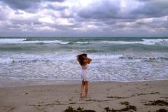 Девушка на предпосылке океана идя и имея праздники на взморье стоковые фото