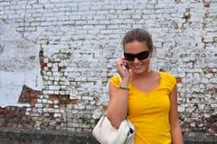 Девушка на предпосылке телефона неровной Стоковые Изображения RF