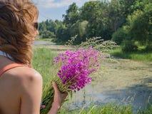 Девушка на природе с рюкзаком и собирает травы стоковое изображение rf
