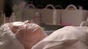 Девушка на процедуре расширять поры и испаряться кожа Горячий пар направлен к стороне женщины в salo косметологии видеоматериал