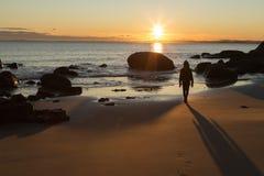 Девушка на пляже во время захода солнца Стоковые Фото