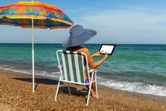 Девушка на пляже работает на самолет-таблице стоковые фото