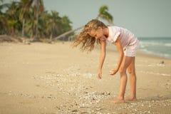 Девушка на пляже собирая раковины стоковые фото