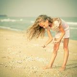 Девушка на пляже собирая раковины стоковые изображения