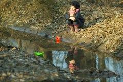Девушка на речном береге играет бумажную шлюпку Стоковые Фото