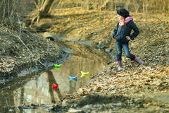 Девушка на речном береге играет бумажную шлюпку Стоковые Изображения