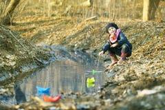 Девушка на речном береге играет бумажную шлюпку Стоковые Изображения RF