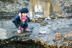Девушка на речном береге играет бумажную шлюпку Стоковое Изображение