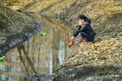 Девушка на речном береге играет бумажную шлюпку Стоковое фото RF