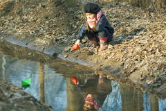 Девушка на речном береге играет бумажную шлюпку Стоковое Изображение RF