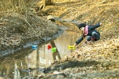Девушка на речном береге играет бумажную шлюпку Стоковая Фотография RF