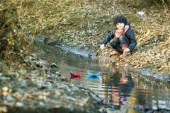 Девушка на речном береге играет бумажную шлюпку Стоковые Фотографии RF
