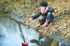 Девушка на речном береге играет бумажную шлюпку Стоковое Фото