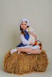 Девушка на сене обнимая зайчика пасхи Стоковое Изображение