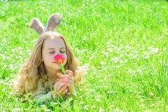 Девушка на спокойной стороне держит красный цветок тюльпана на солнечный весенний день Ребенок наслаждается ароматностью тюльпана Стоковая Фотография RF