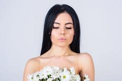 Девушка на спокойной стороне стоит нагой и держит цветки стоцвета перед концепцией заботы кожи комода Женщина с ровной Стоковое Фото