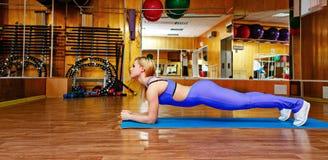 Девушка на спортзале делая тренировки на циновке Стоковое Фото