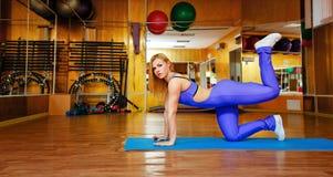Девушка на спортзале делая тренировки на циновке Стоковые Изображения
