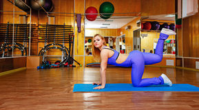 Девушка на спортзале делая тренировки на циновке Стоковое Изображение