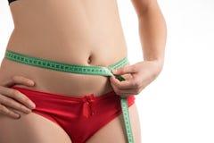 Девушка на талии диеты измеряя и сантиметре и взглядах брюшка стоковое фото