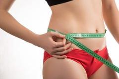 Девушка на талии диеты измеряя и сантиметре и взглядах брюшка стоковые фотографии rf