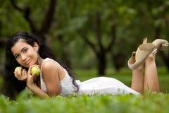 Девушка на траве и яблоках Стоковое фото RF