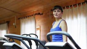 Девушка на тренере фитнеса на спортзале видеоматериал