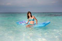 Девушка на тюфяке на воде стоковая фотография