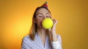 Девушка надувая воздушный шар на желтой предпосылке акции видеоматериалы