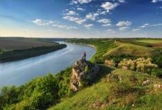 Девушка на утесе над рекой Стоковая Фотография