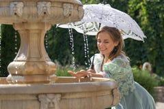 Девушка на фонтане с белым зонтиком Стоковое Фото