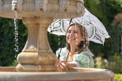 Девушка на фонтане с белым зонтиком Стоковые Изображения RF