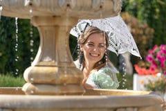 Девушка на фонтане с белым зонтиком Стоковые Фотографии RF